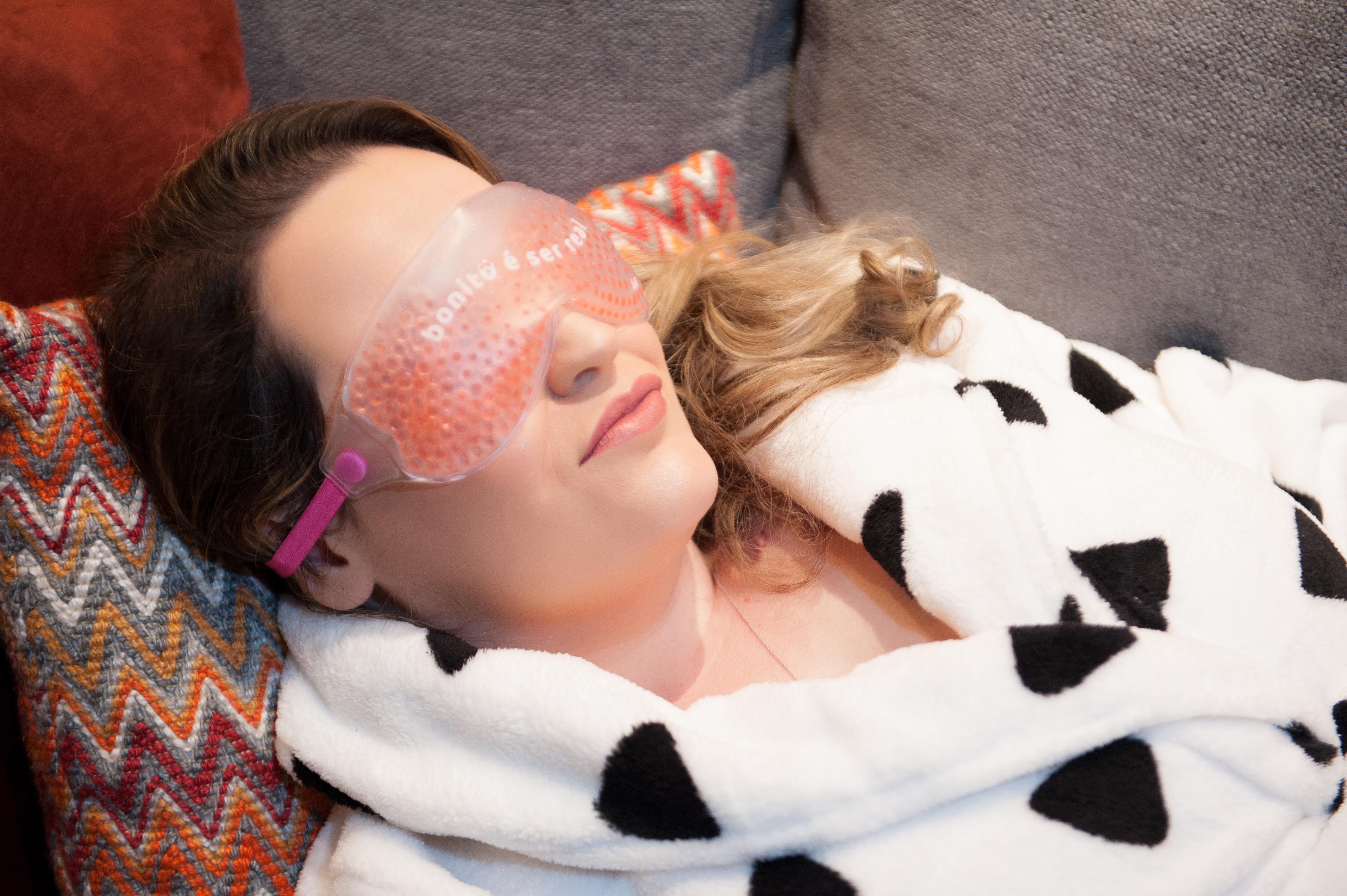 A foto apresenta uma mulher deitada usando um tapa olhos