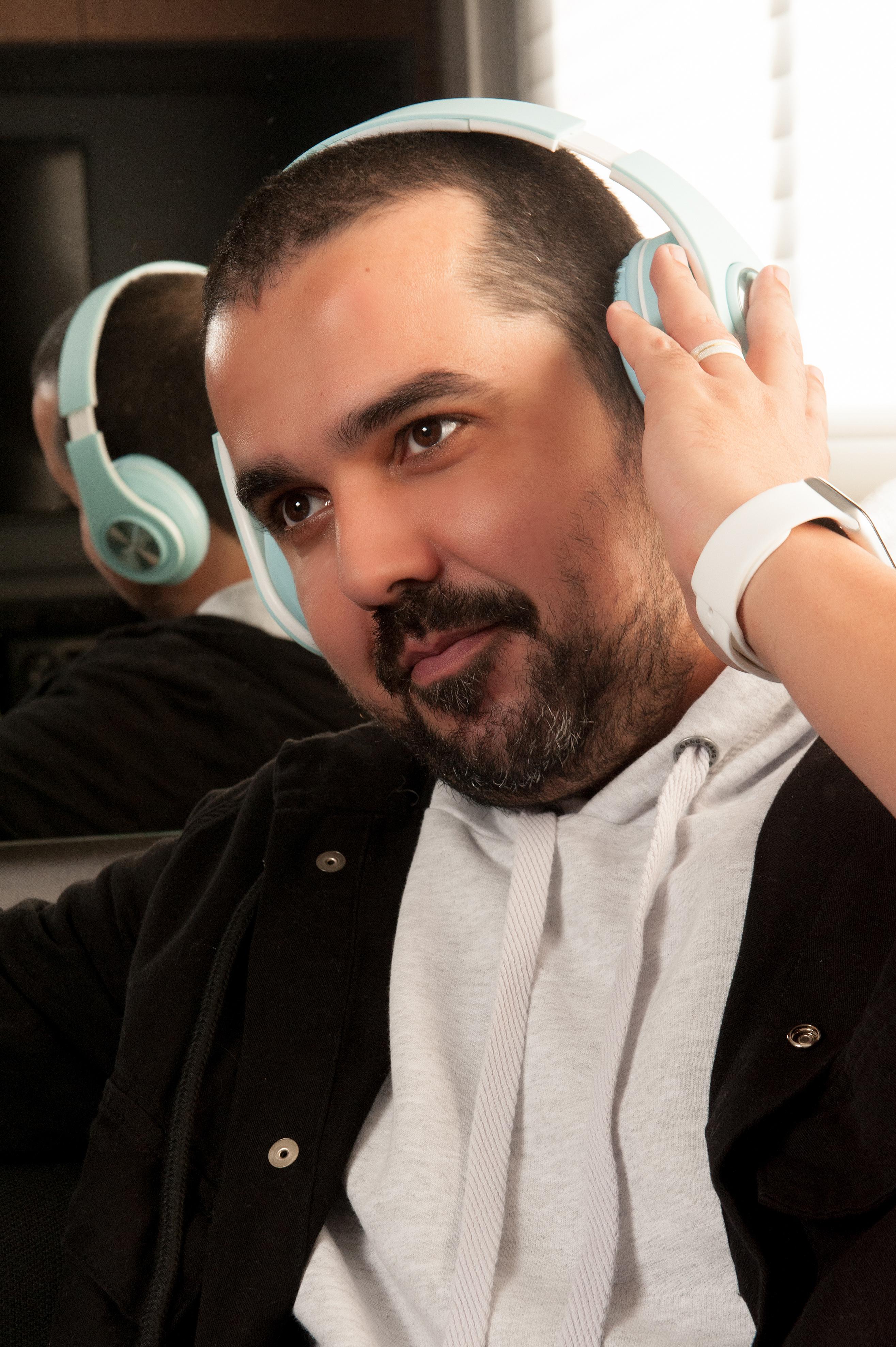 A foto apresenta um homem com um headphone