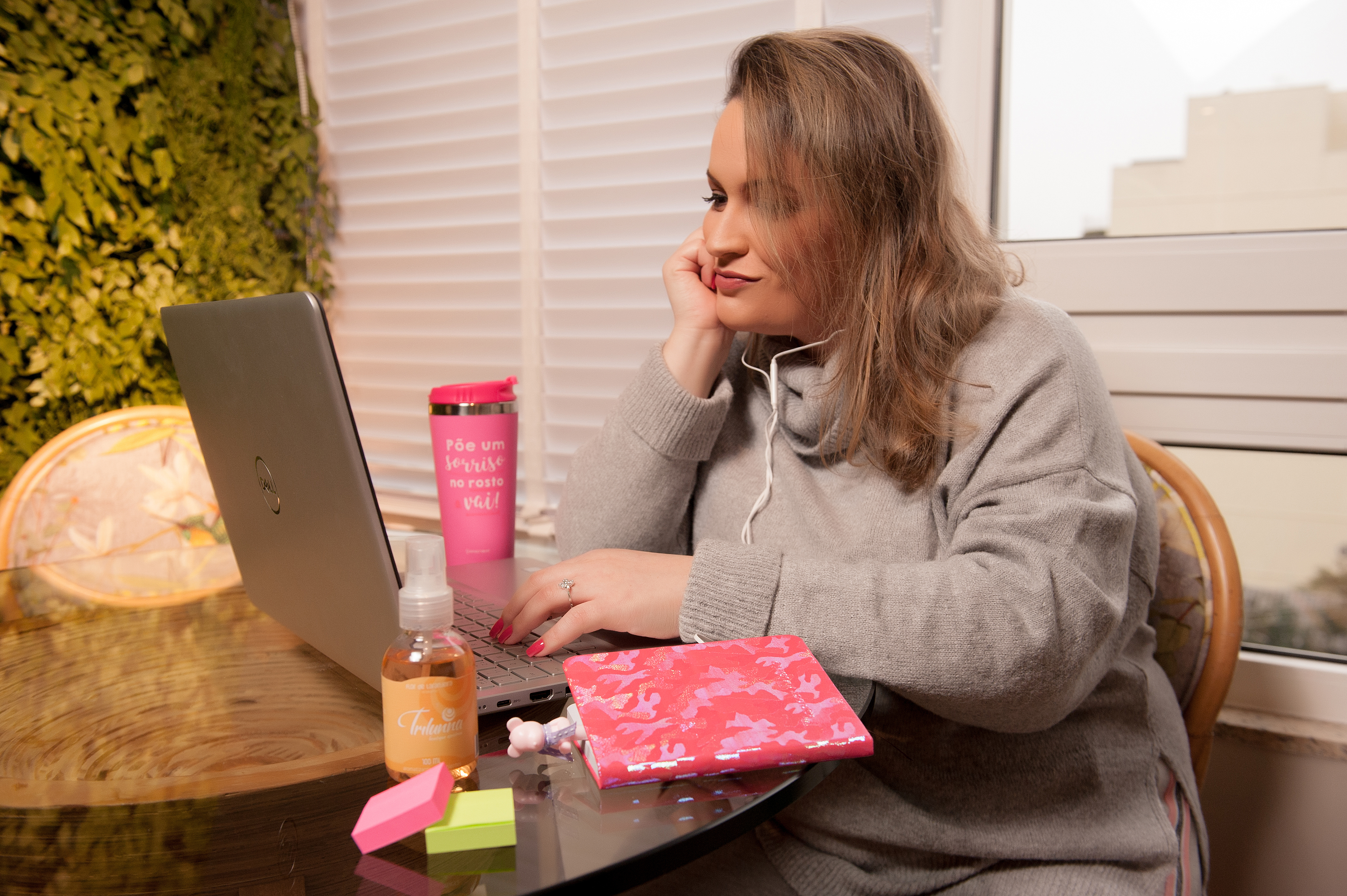 A imagem mostra uma mulher mexendo no computador e usando fones de ouvido