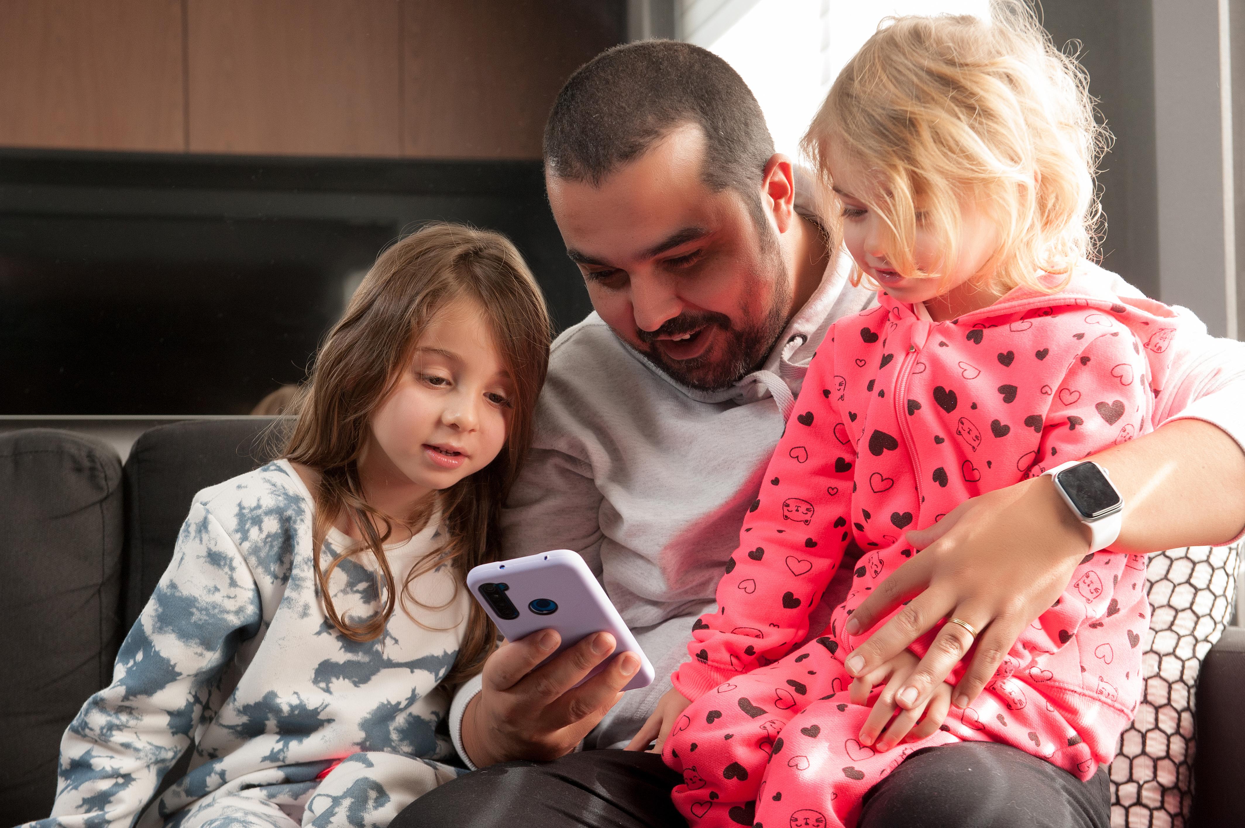 A foto mostra o pai com duas filhas pequenas mexendo no celular