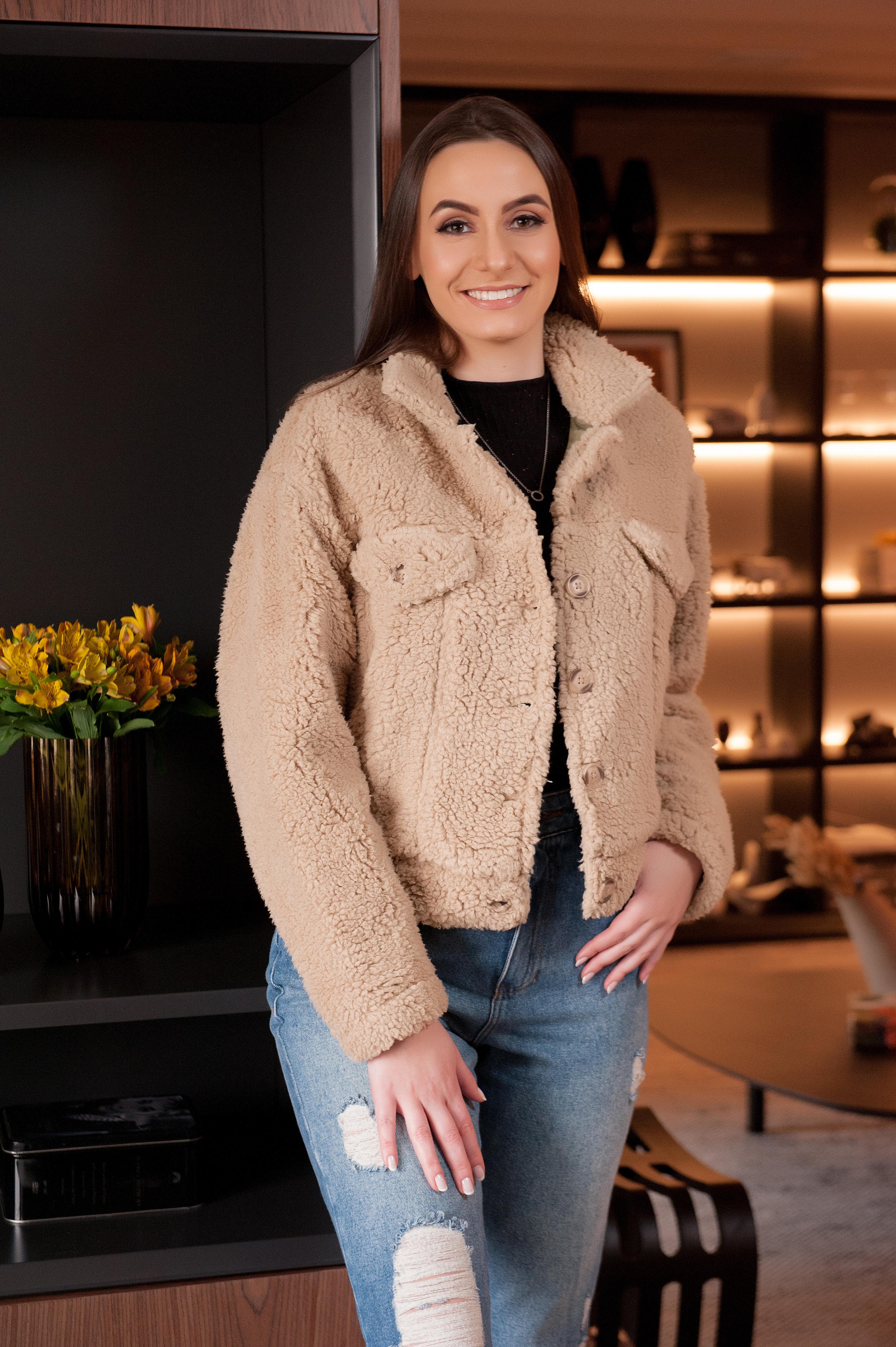 A modelo está usando uma blusa preta, um casaco de pelo bege e calça jeans azul.