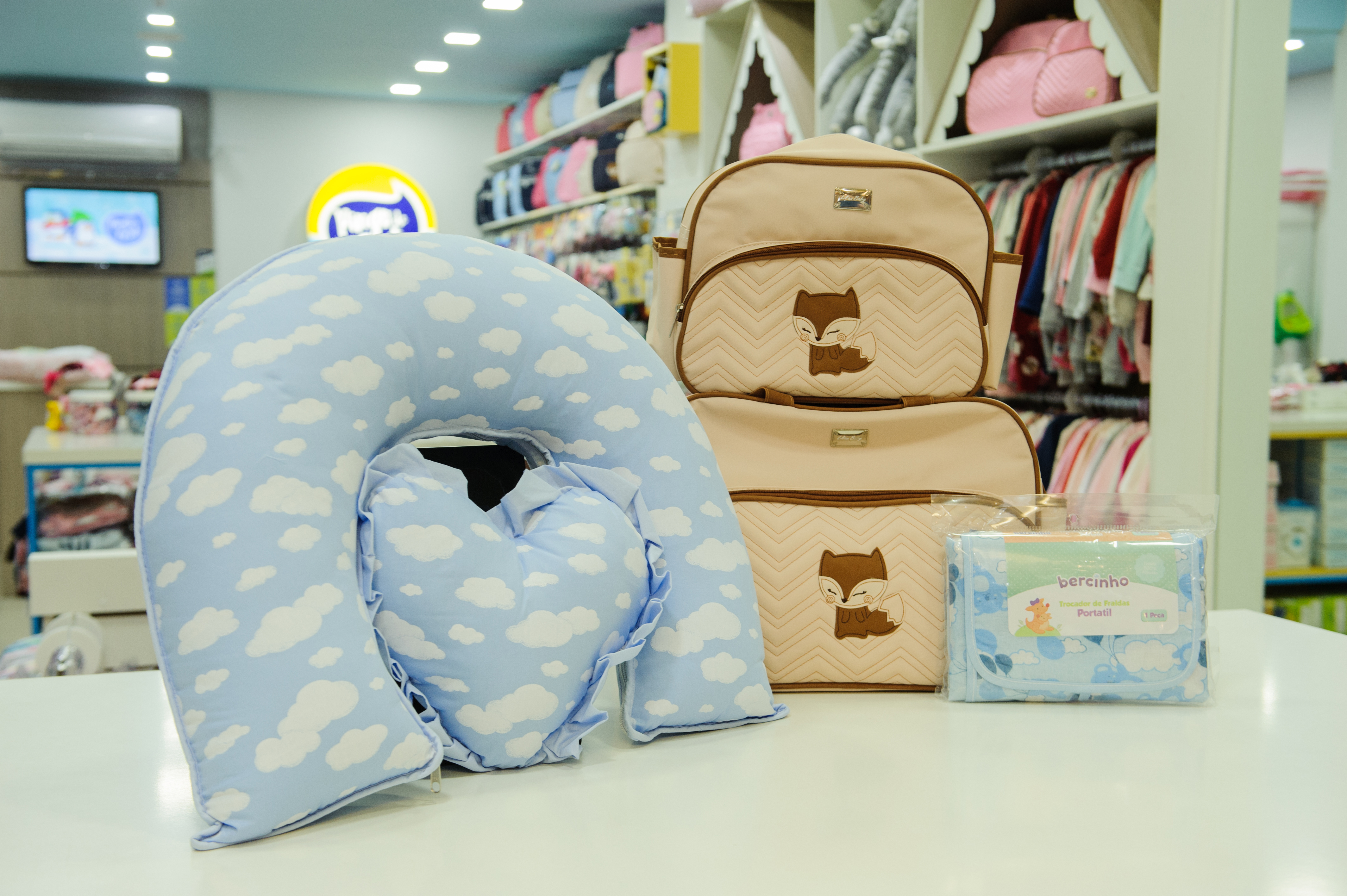 A foto mostra um travesseiro para amamentação, bolsa para maternidade e trocador de fraldas portátil.