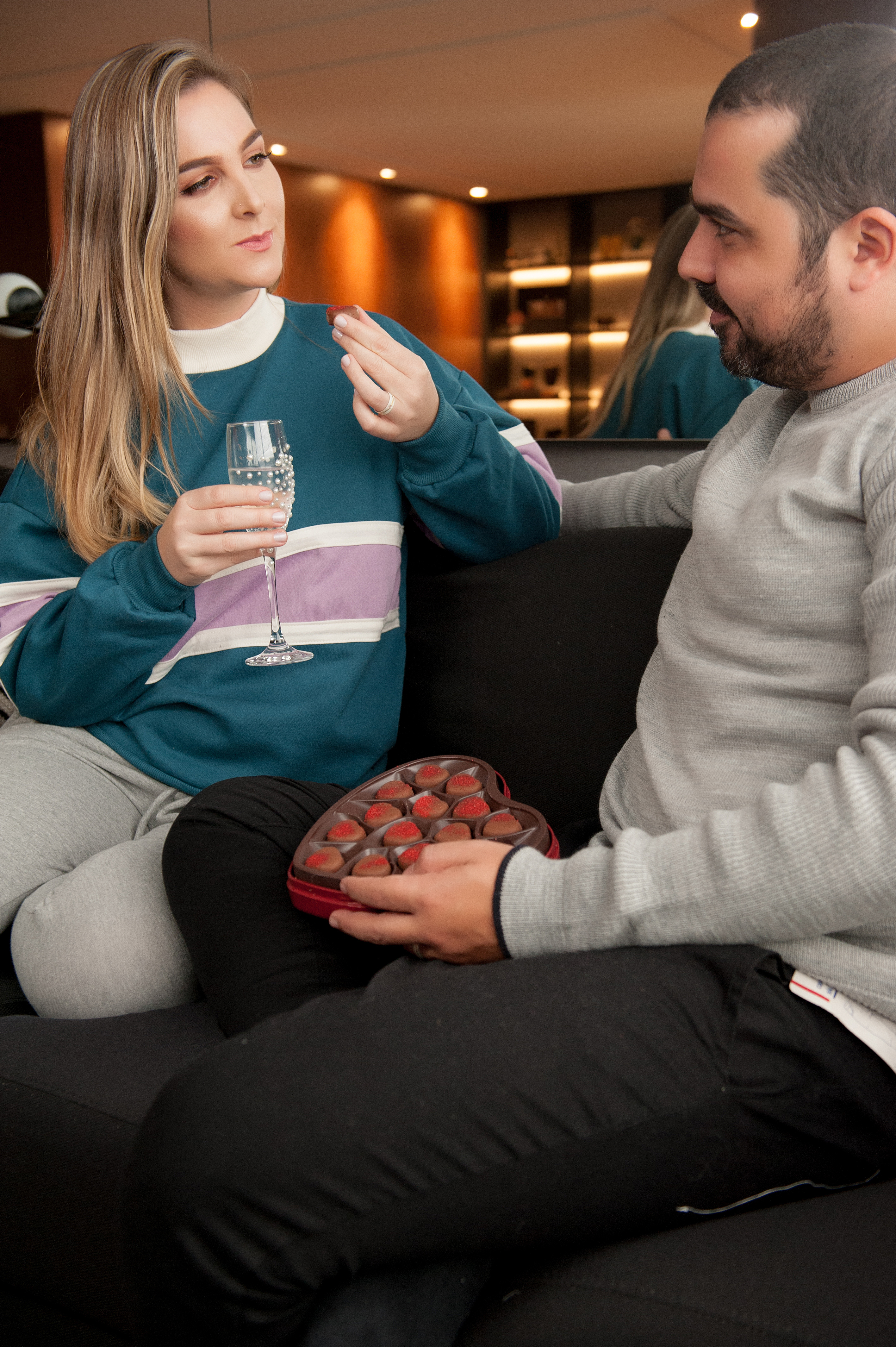 A imagem é de um casal, um ao lado do outro, comendo chocolates