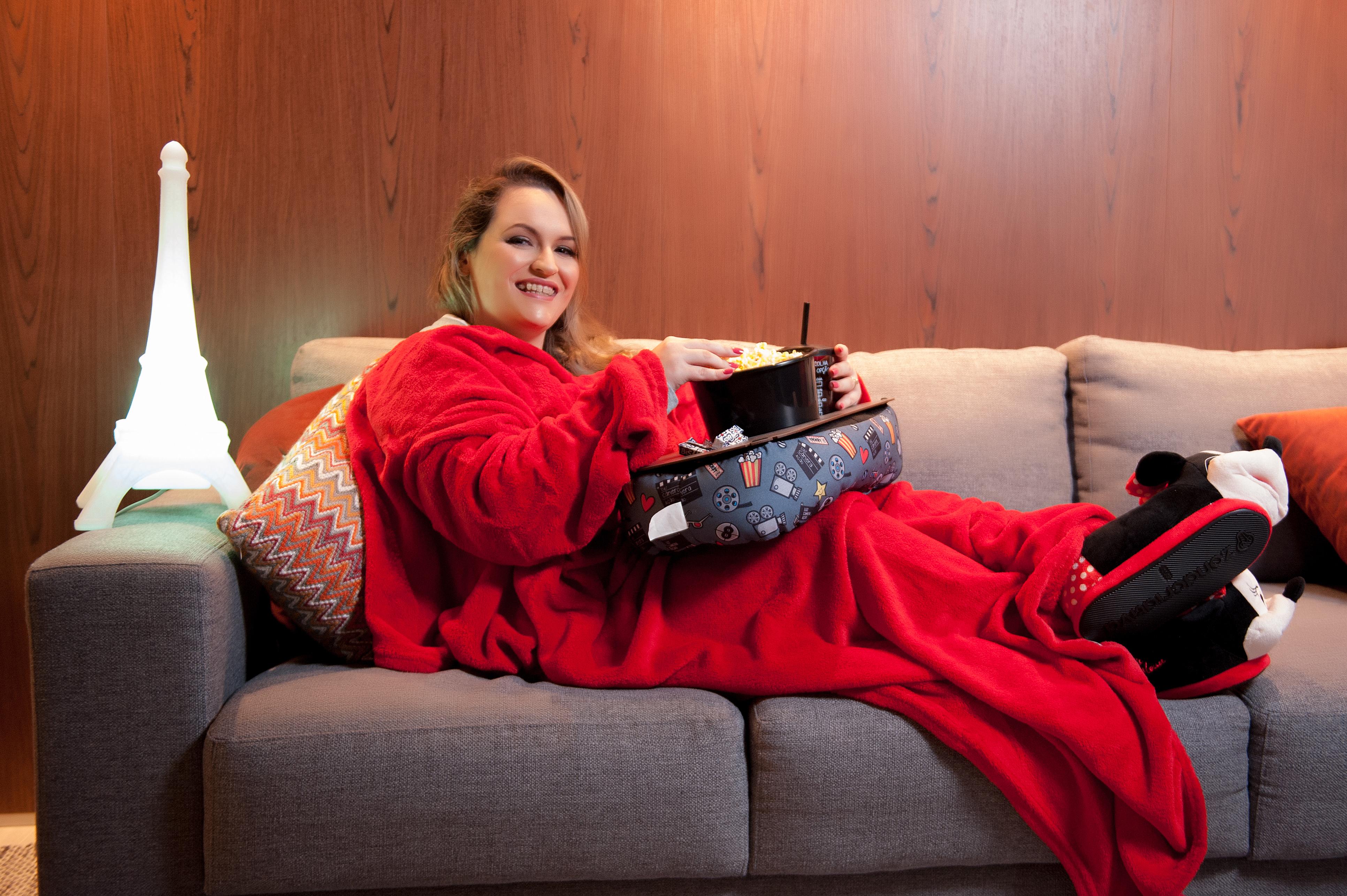 A imagem é de uma mulher deitada no sofá com cobertor e porta pipocas.