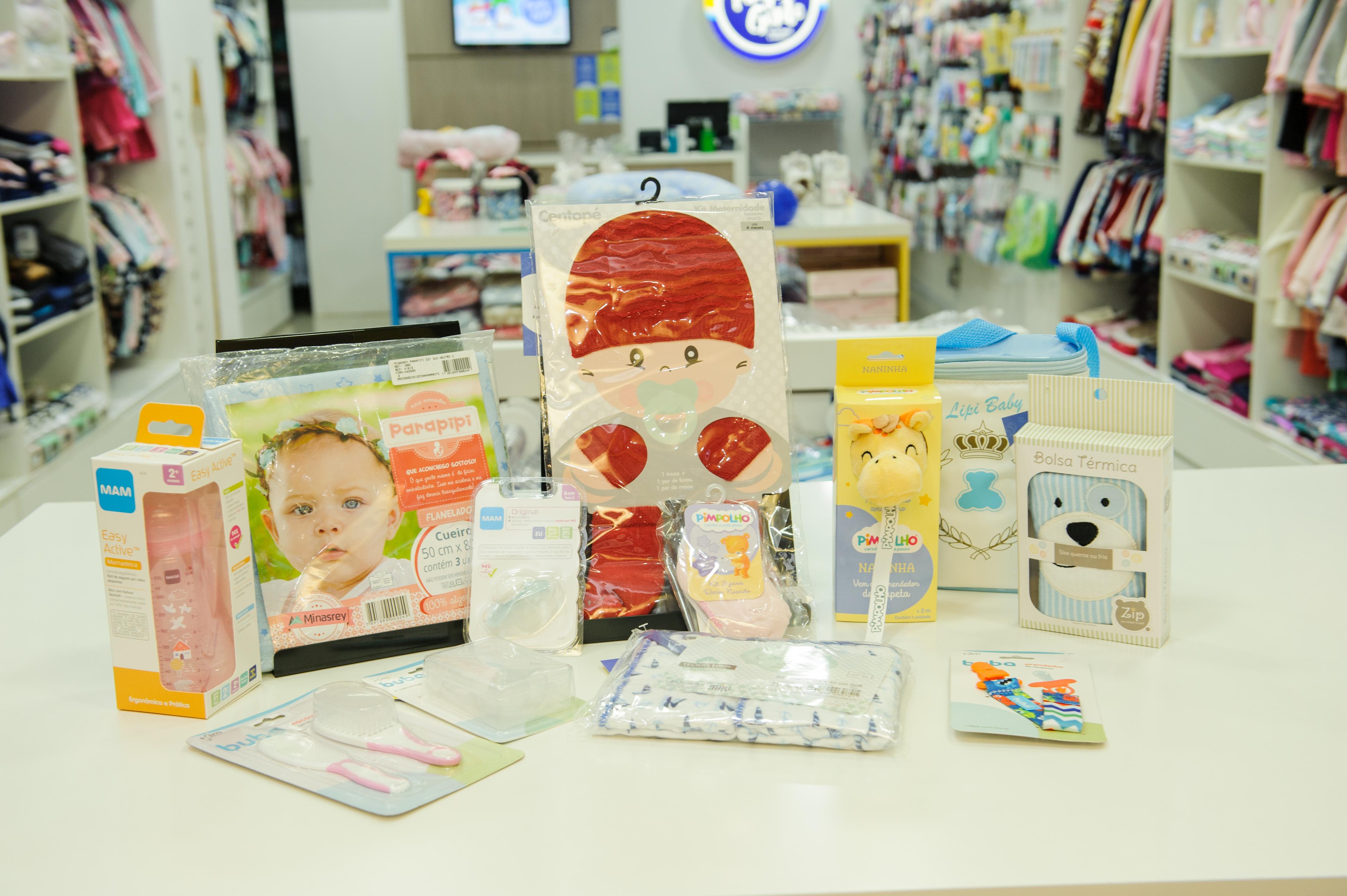 A imagem apresenta mamadeira, cueiro, chupeta, prendedor de chupeta, meia, naninha, bolsa térmica, escova de cabelo, meia e luvas para bebê.