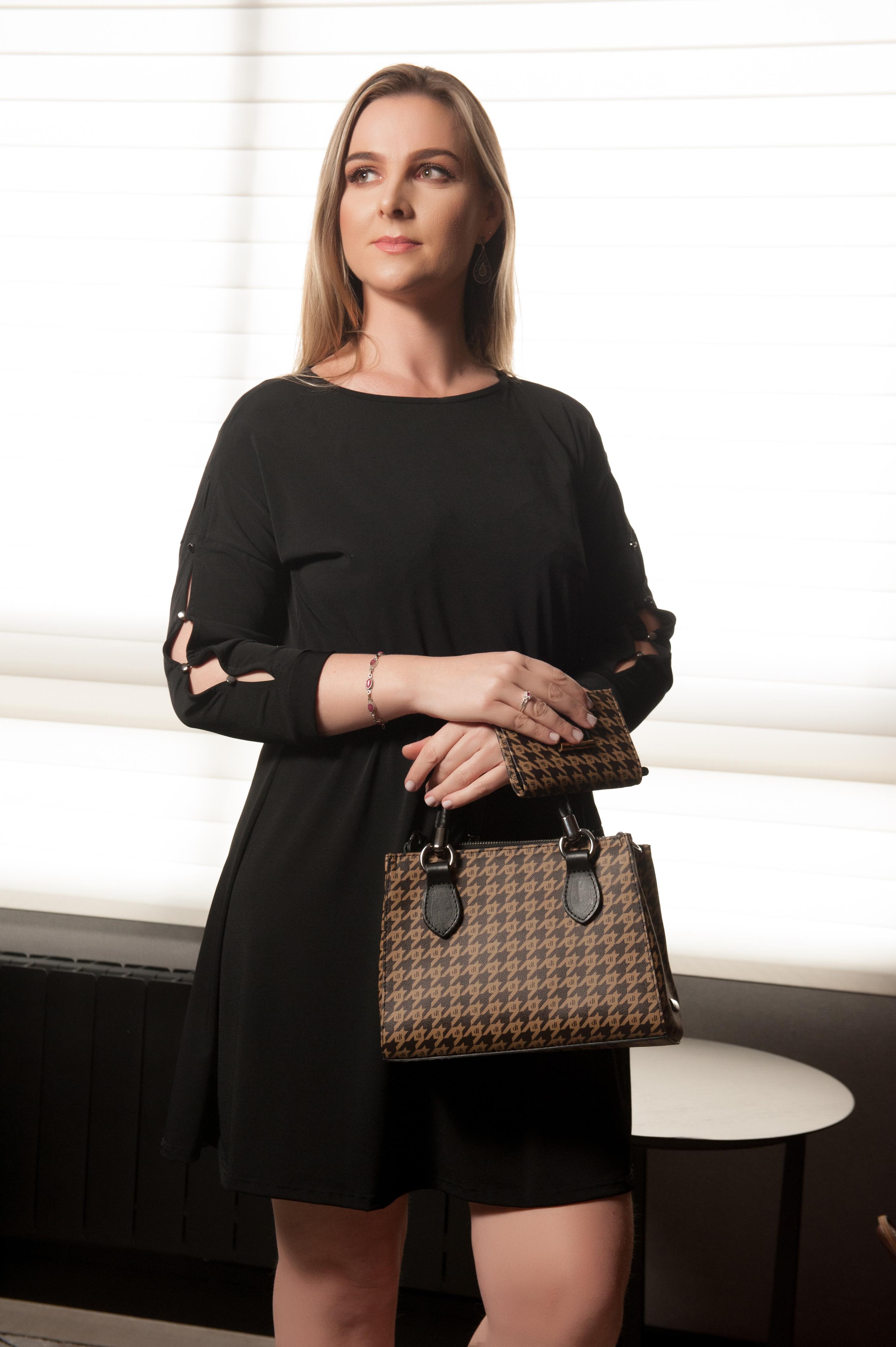A modelo está usando um vestido preto e segurando uma carteira e uma bolsa.