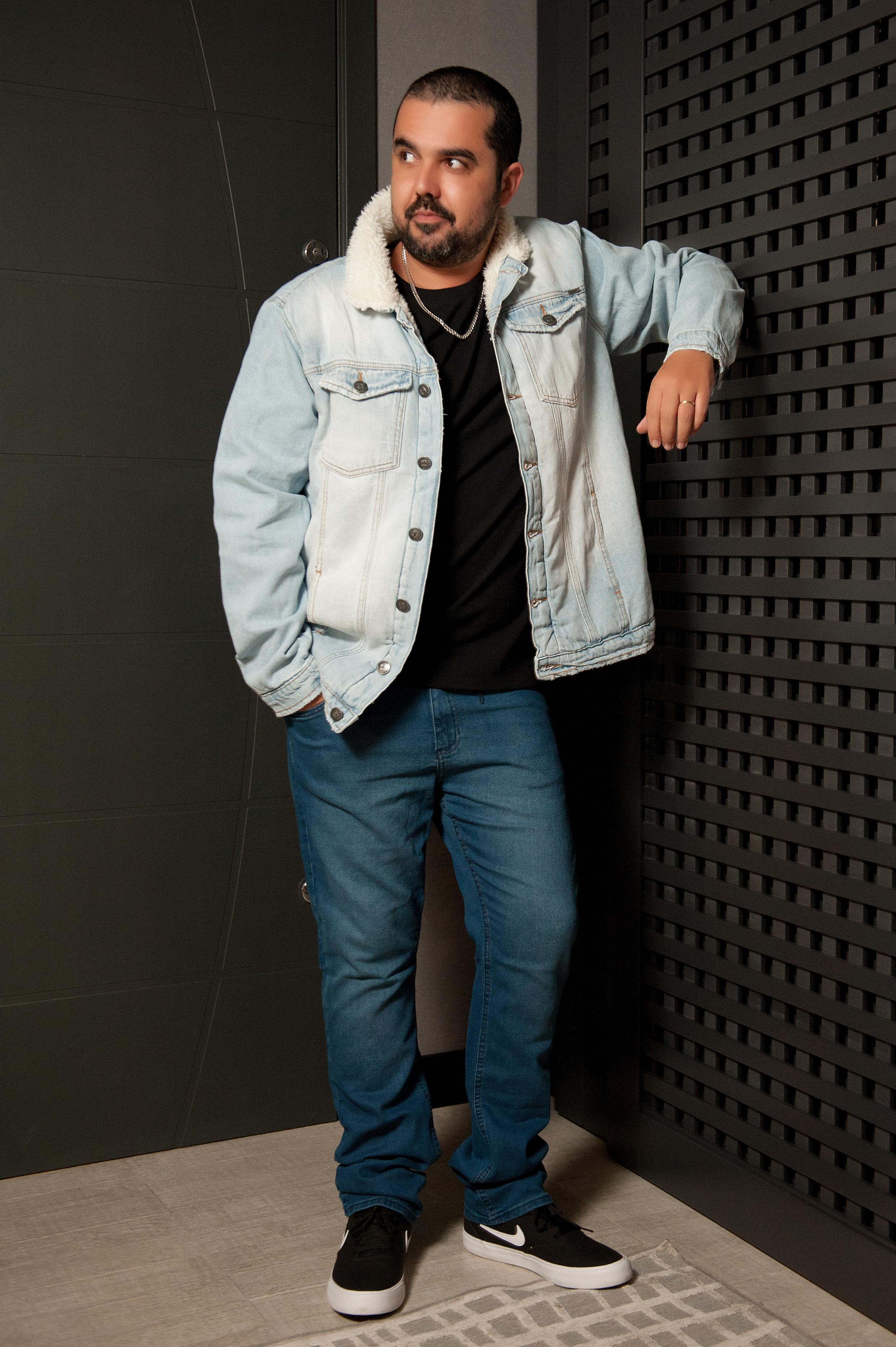O modelo está usando blusa preta, jaqueta e calça jeans azuis e tênis preto e branco.