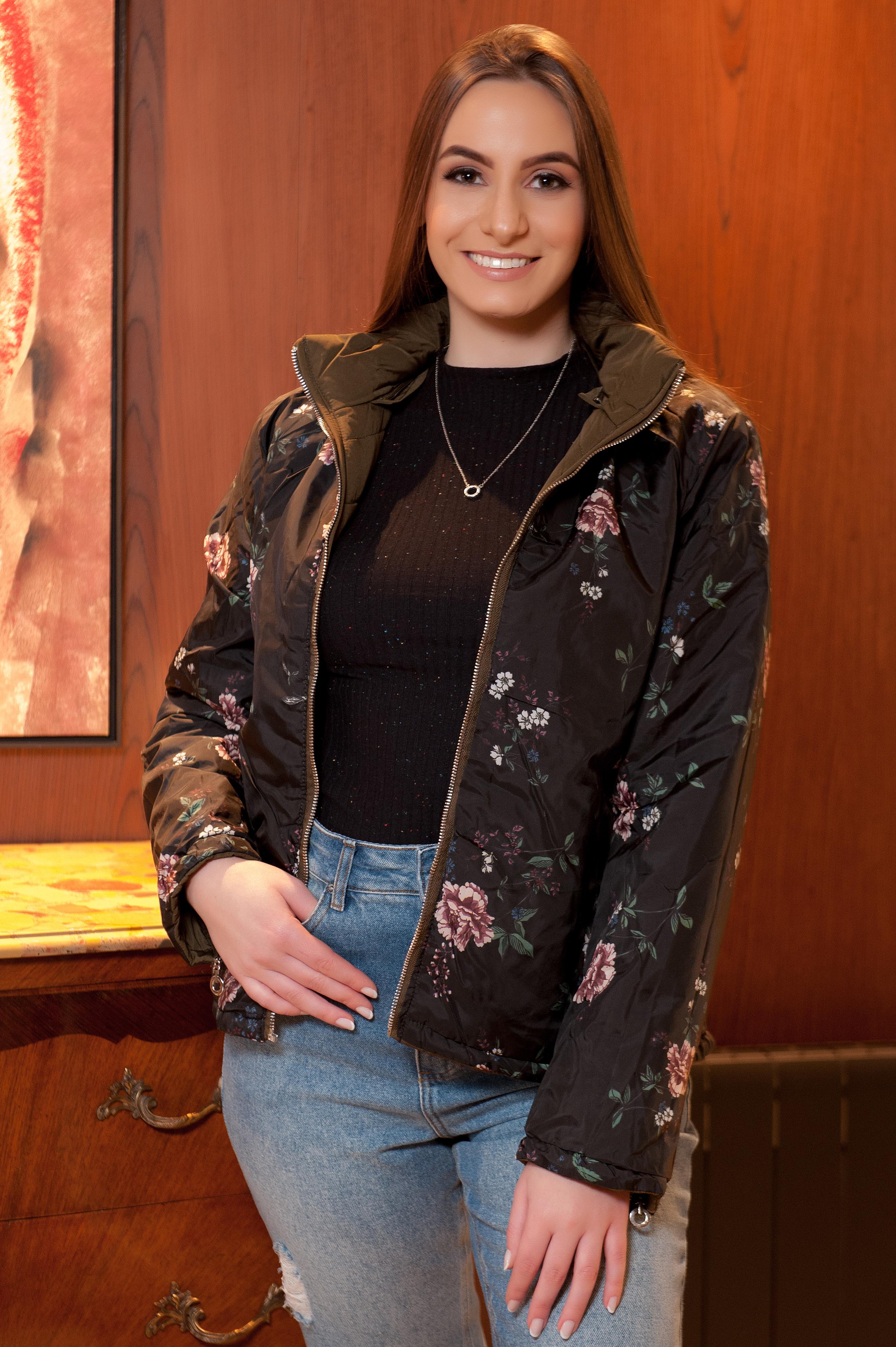 A modela está vestindo uma blusa de gola alta preta, uma jaqueta floral e calça jeans azul.