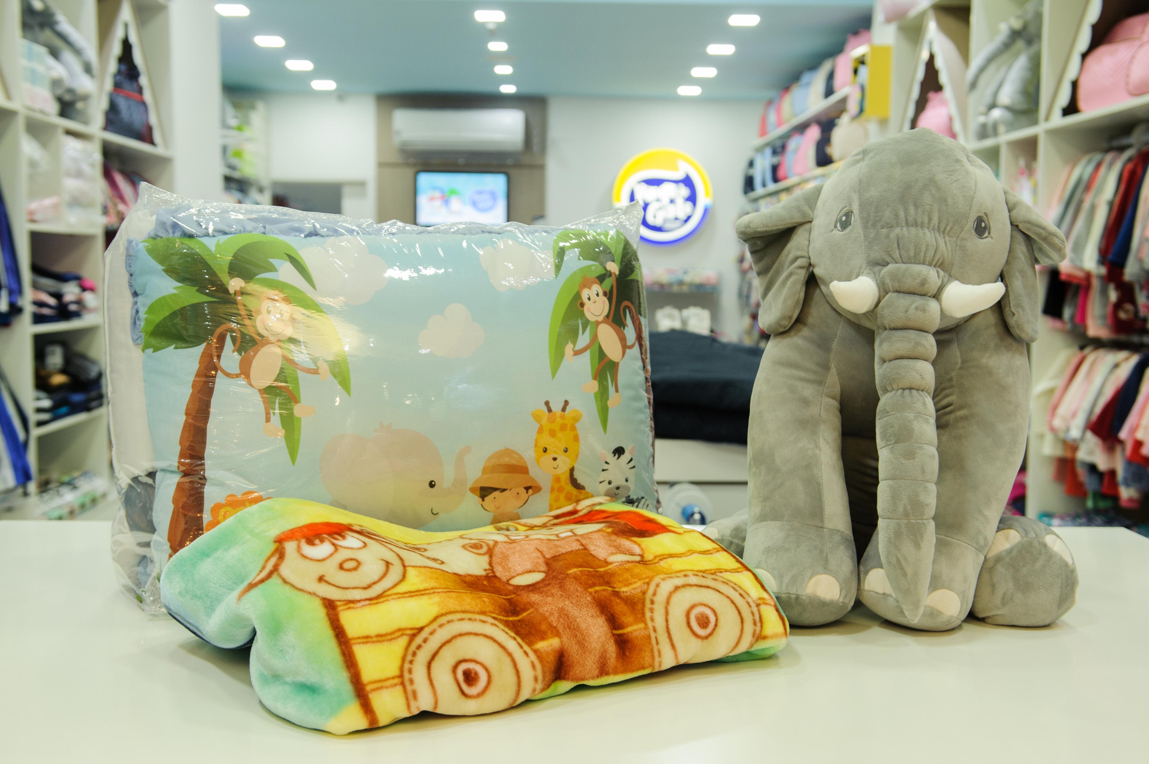 A foto mostra um conjunto de cama com desenho de animais e um elefante de pelúcia ao lado.