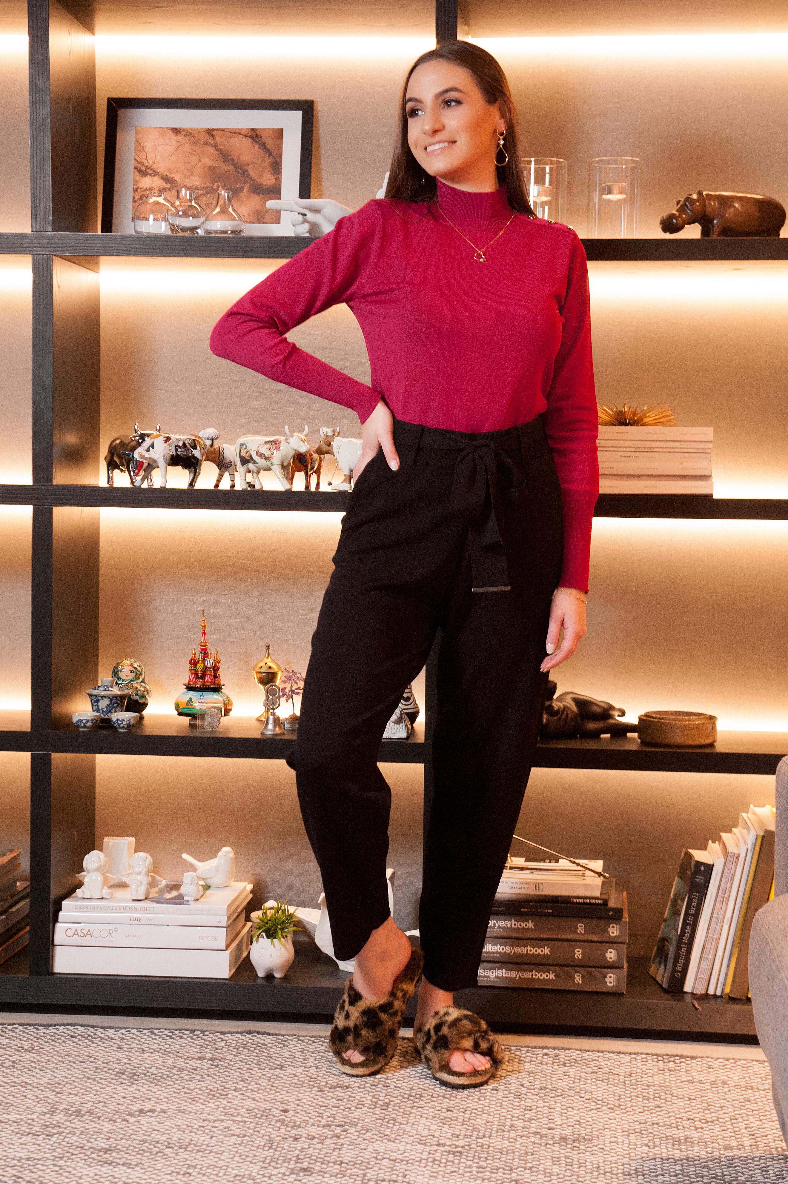 A modelo está usando uma blusa rosa de gola alta, calça preta e chinelo de pelo.